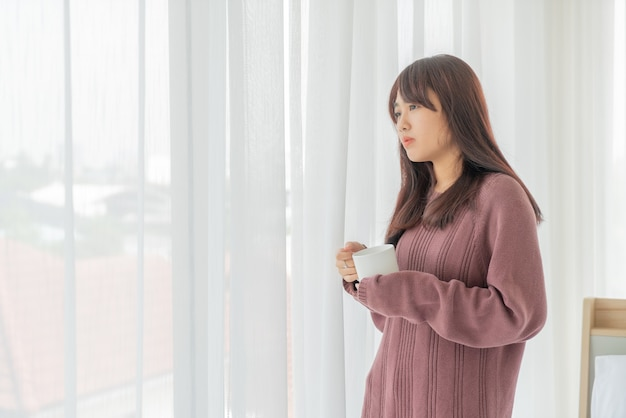 Mooie aziatische vrouwen die 's ochtends koffie drinken