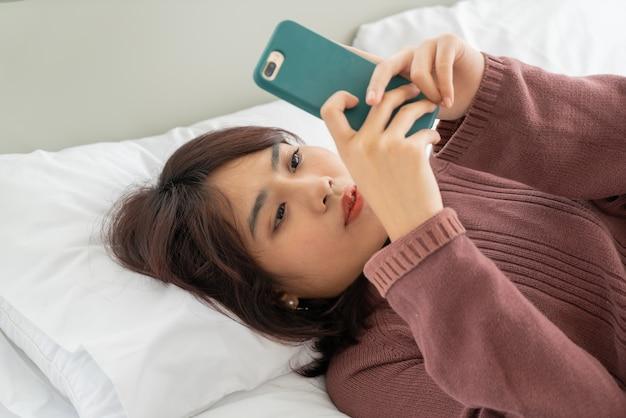 Mooie aziatische vrouwen die smartphone op bed spelen