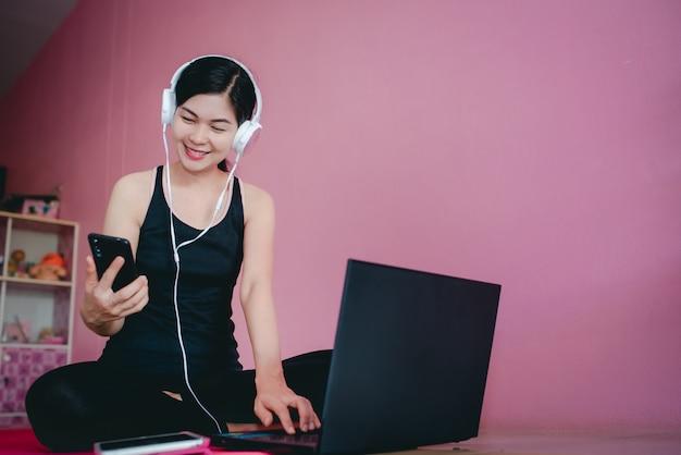 Mooie aziatische vrouwen dragen een koptelefoon om te sporten in zwarte sportkleding, zitten kijken naar video's, oefenen thuis en notebooks.