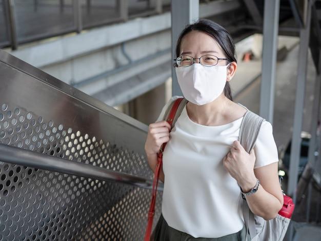 Mooie aziatische vrouwen dragen elke keer buitenshuis een wegwerp medisch gezichtsmasker, als een nieuwe normale trend en zelfbescherming