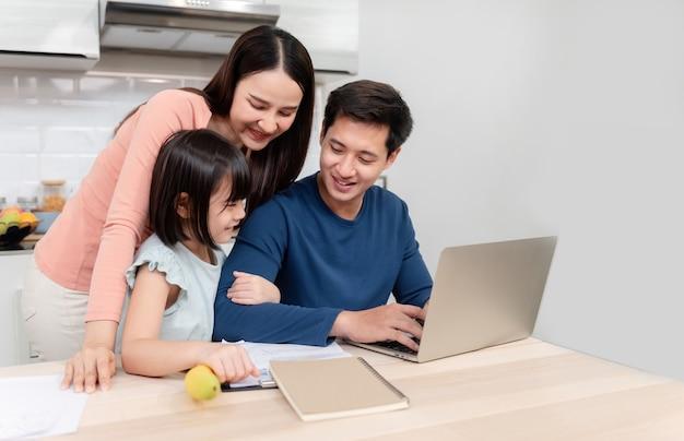 Mooie aziatische vrouwen mooi meisje kijkend naar het laptopscherm van knappe mannen die thuis online aan het bureau werken het is een nieuw normaal leven voor het gezin.
