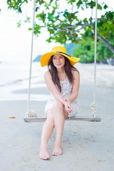 Mooie aziatische vrouwen reizen op het strand in de zomer. zee zand zon en vakantie.