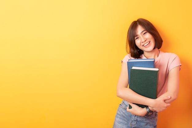 Mooie aziatische vrouwen universitaire student gelukkig op gele muur