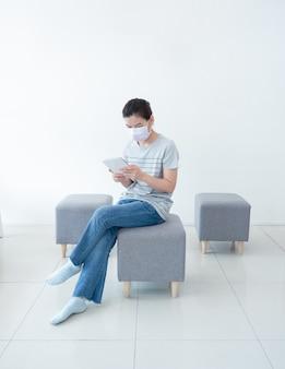 Mooie aziatische vrouwen werken thuis met behulp van tablet, comfortabel zittend op de bank, tijdens quarantaine in pandemie van coronavirus. werken vanuit huis en sociaal afstandsconcept.