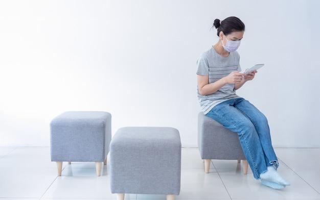 Mooie aziatische vrouwen werken thuis met behulp van tablet om te vergaderen met online team, comfortabel zittend op de bank, tijdens quarantaine in pandemie van coronavirus