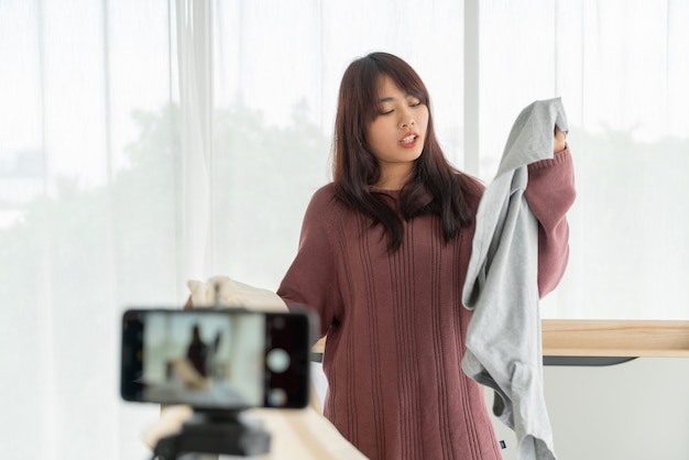 Mooie aziatische vrouwenblogger die kleren op camera toont om live vlog op te nemen in haar winkel