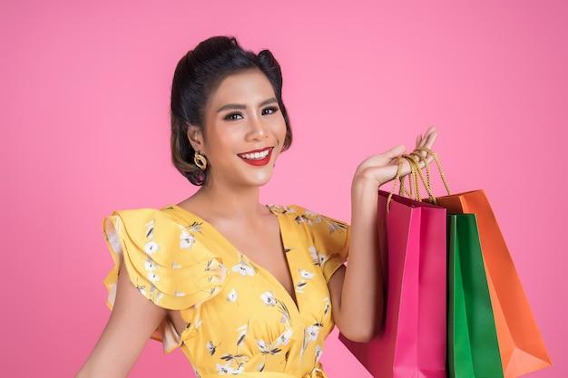 Mooie aziatische vrouwenholding gekleurde het winkelen zakken