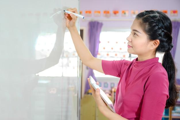 Mooie aziatische vrouwenleraar die op het witte bord schrijft die studenten op school in de klas lesgeeft voor onderwijs
