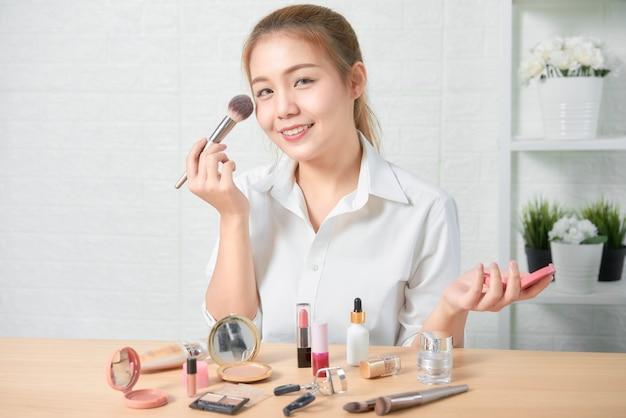 Mooie aziatische vrouwenmake-up met schoonheidsmiddelenproducten.