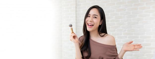 Mooie aziatische vrouwenschoonheid blogger die een make-up leerprogramma doet