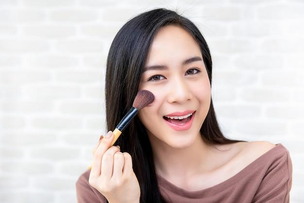 Mooie aziatische vrouwenschoonheid blogger die make-upleerprogramma doet