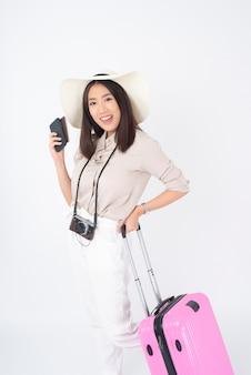 Mooie aziatische vrouwentoerist op witte muur