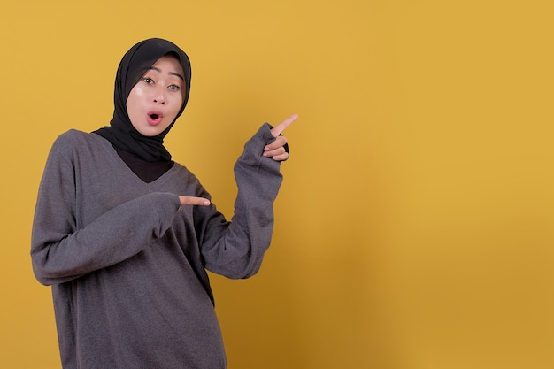Mooie aziatische vrouwenverrassing en iets richten met behulp van casual t-shirt
