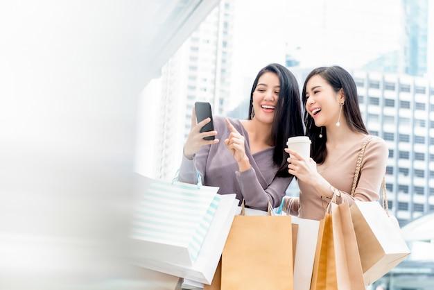 Mooie aziatische vrouwenvrienden die smartphone gebruiken terwijl het winkelen in de stad