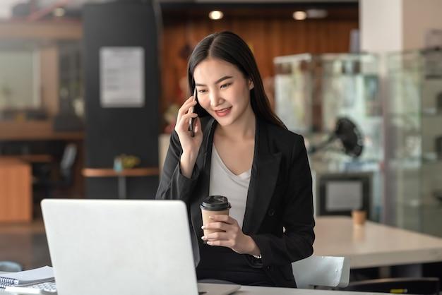 Mooie aziatische zakenvrouw die aan de telefoon praat en koffie vasthoudt tijdens het chatten met klanten op kantoor.