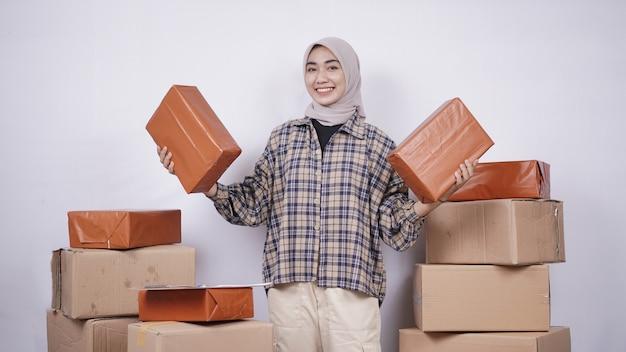 Mooie aziatische zakenvrouw die pakketten toont die gelukkig op witte achtergrond worden geïsoleerd