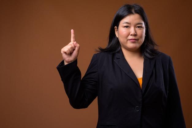 Mooie aziatische zakenvrouw met overgewicht op bruin