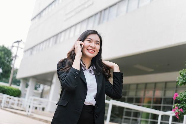 Mooie aziatische zakenvrouw praten over mobiel tijdens het wandelen buiten