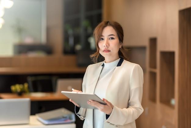Mooie aziatische zakenvrouw staande bedrijf tablet.