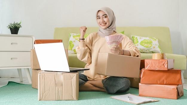 Mooie aziatische zakenvrouw verdient gelukkig geld van haar harde werk