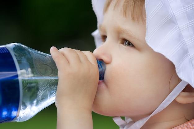 Mooie baby heeft water uit een plastic fles
