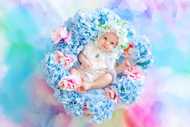 Mooie baby in een hoed gemaakt van bloemen liggend in een mand met hortensia's op een blauwe achtergrond