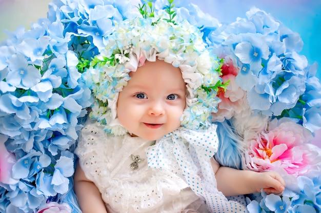Mooie baby in een hoed gemaakt van bloemen liggend in een mand met hortensia's
