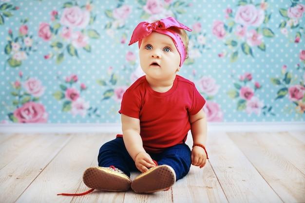 Mooie baby in een roze jas en jeans zittend op de vloer. ouderschap.