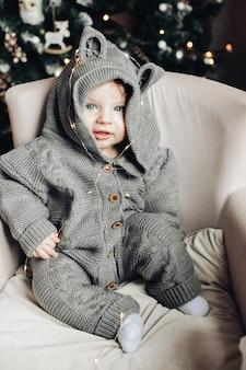 Mooie baby in gebreide onesie zittend in zachte fauteuil met mooie kerstboom. vakantie concept