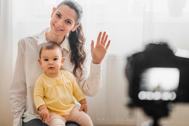 Mooie baby peuter met jonge moeder voor de camera vloggen of bloggen