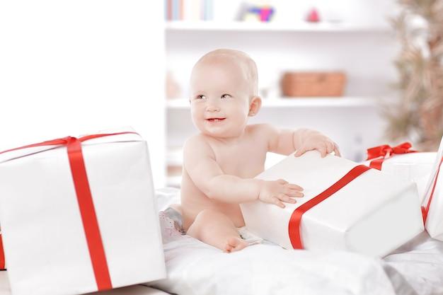 Mooie baby speelt met geschenkdozen zittend op de bank