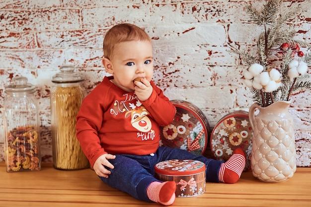 Mooie baby zit aan tafel en eet een noot