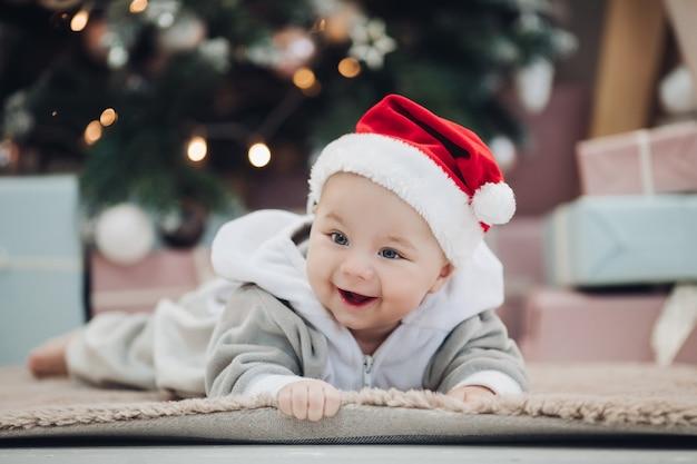 Mooie babyjongen die in grijs kostuum en rode kerstmanhoed op tapijt tegen vage kerstmisboom legt.