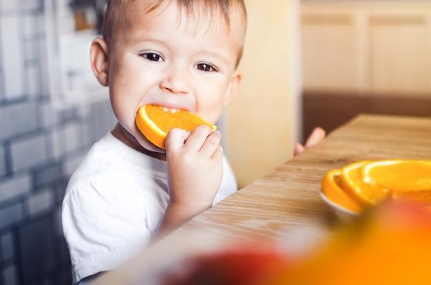 Mooie babyjongen in de keuken die gretig een sinaasappel eet, in partjes gesneden