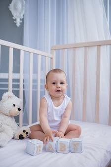 Mooie babyjongen in een witte bodysuit zit in een wieg met speelgoed en kijkt naar de camera