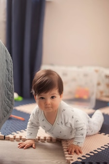 Mooie babyjongen met donker haar in de lichte pyjama's leren kruipen en liggen op zijn buik op de vloer in de kinderkamer