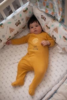 Mooie babyjongen met donker haar in een geel lichaam liggend in een bedje