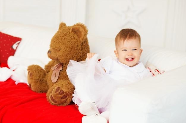 Mooie babymeisje lachen en plezier zittend op de bank in het interieur met kerstversiering.