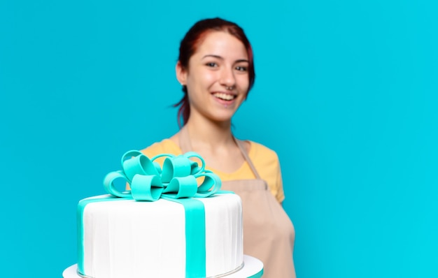Mooie bakkersmedewerker met een verjaardagstaart