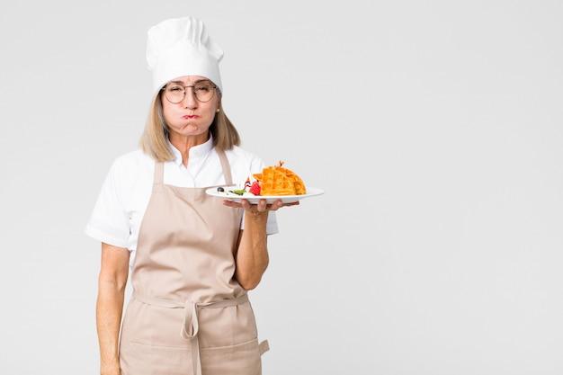 Mooie bakkersvrouw op middelbare leeftijd met wafels tegen muur