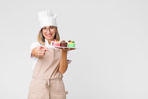 Mooie bakkersvrouw van middelbare leeftijd met cakes tegen exemplaar ruimtemuur
