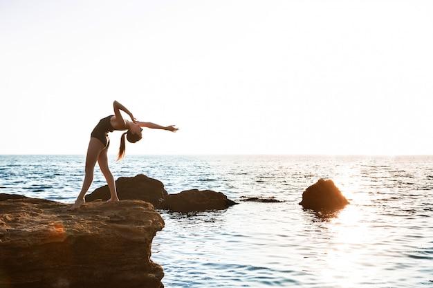 Mooie ballerina dansen, die zich voordeed op rots op het strand, uitzicht op zee.