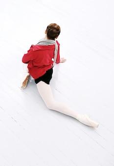 Mooie ballerina die zich uitstrekt over de vloer