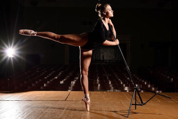 Mooie ballerina in pointe-schoenen flap been hand in hand op het rek in het werkgebied maken