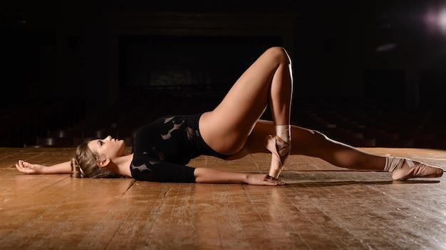Mooie ballerina in pointe-schoenen ligt op zijn achtergebogen been op het podium