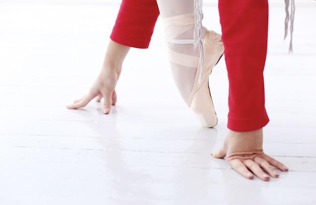 Mooie ballerina in rood balancerend op één voet