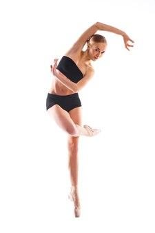 Mooie ballerina poseren pn wit oppervlak in trainingspak