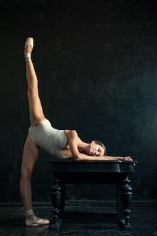 Mooie ballerina poseren tegen donker