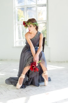 Mooie ballerina zittend in lange grijze jurk