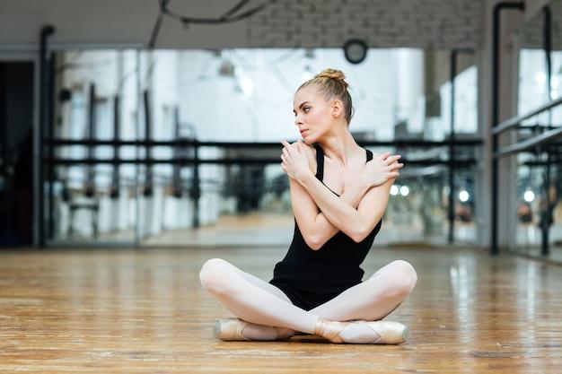Mooie ballerina zittend op de vloer in balletles